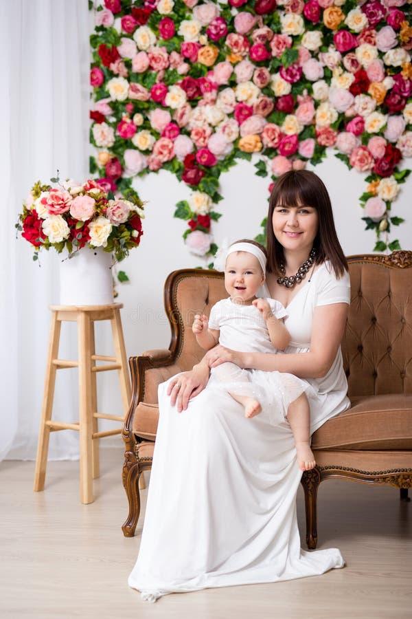 母亲节概念-有逗人喜爱的矮小的女儿的愉快的美丽的母亲坐在花墙壁的葡萄酒沙发 免版税库存图片