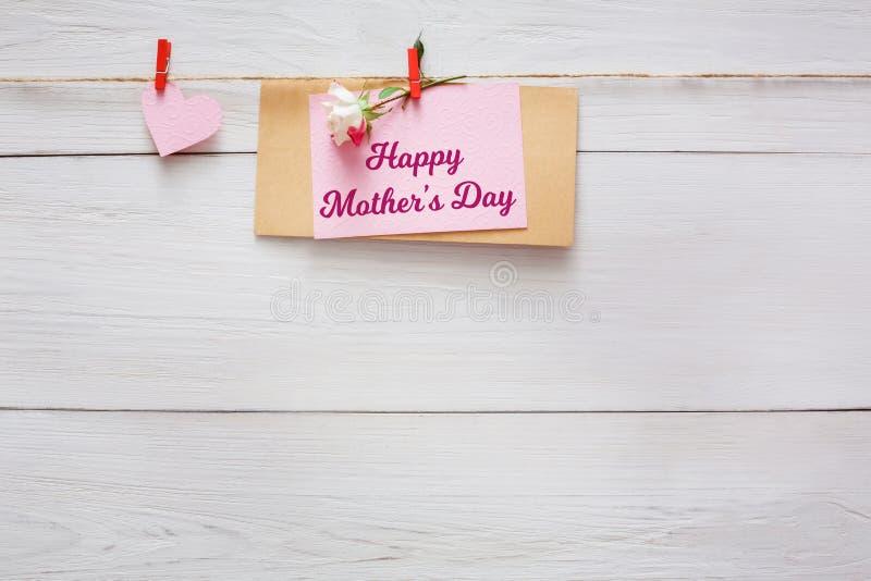 母亲节背景、心脏和纸牌在晒衣夹在木枕头心脏边界在木头,拷贝空间 免版税图库摄影