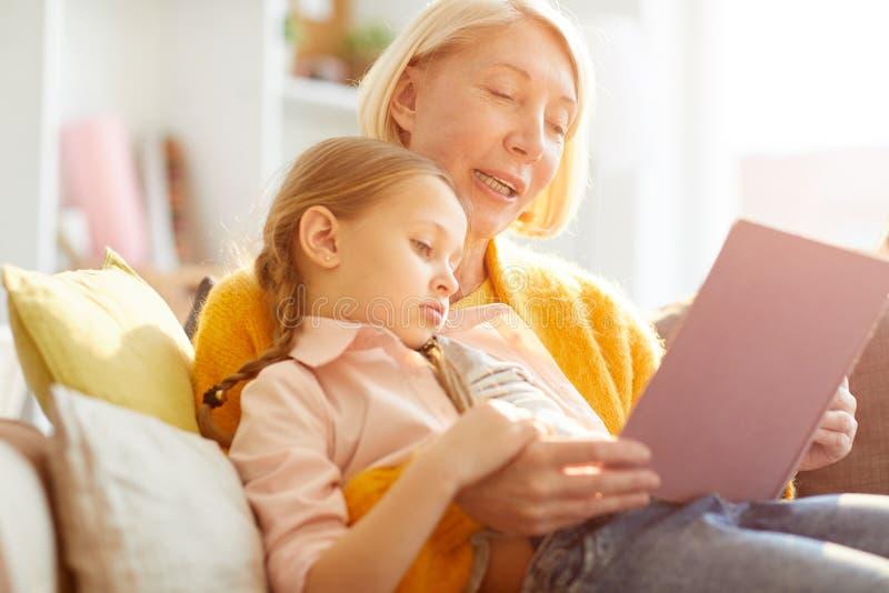 母亲读书故事在阳光下 免版税库存照片