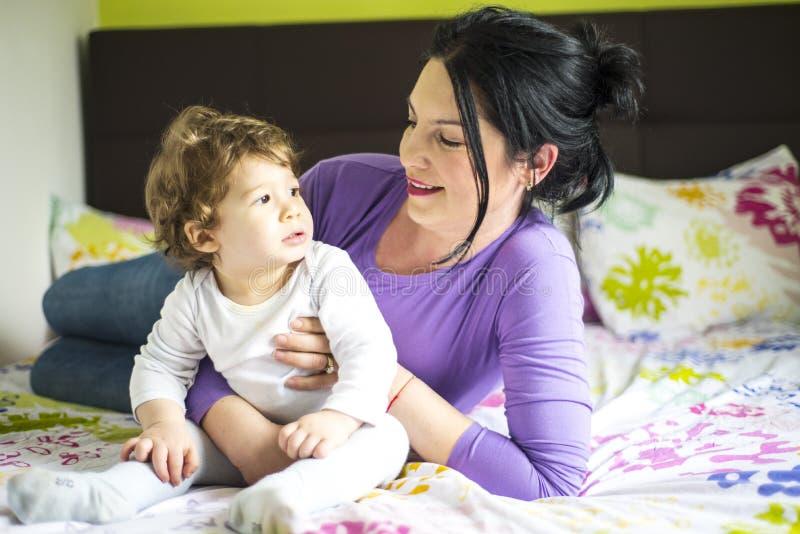母亲谈话与小儿子在床上 免版税库存图片