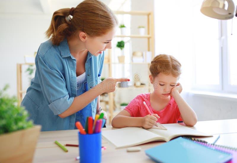 母亲责骂恶劣的教育和家庭作业的一个孩子 免版税库存照片