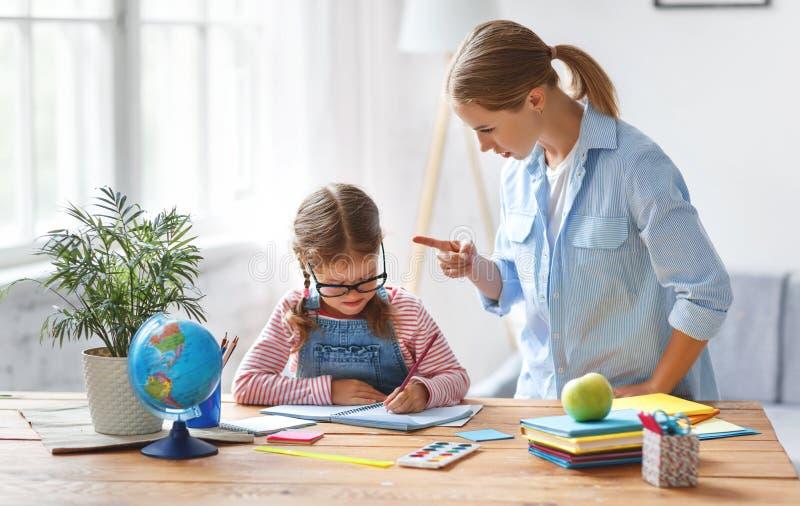 母亲责骂贫寒教育和家庭作业的一个孩子 免版税图库摄影