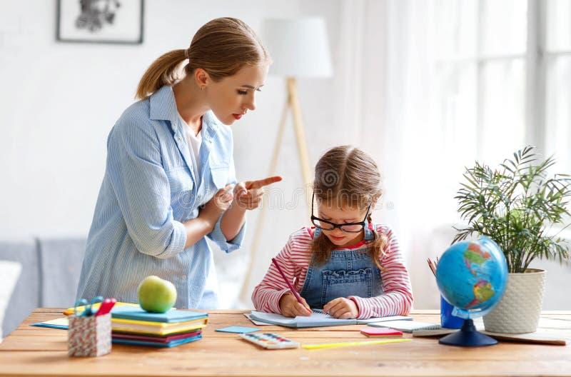 母亲责骂贫寒教育和家庭作业的一个孩子 库存照片