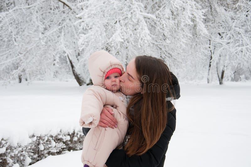 母亲走与她的女儿在街道上的冬天 库存图片