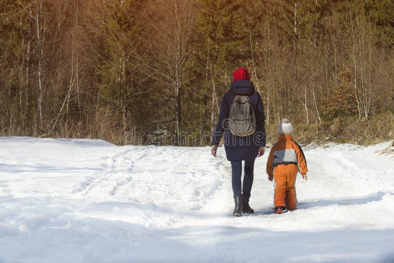 母亲走沿积雪的路的withlittle儿子以具球果森林冬日为背景 免版税图库摄影