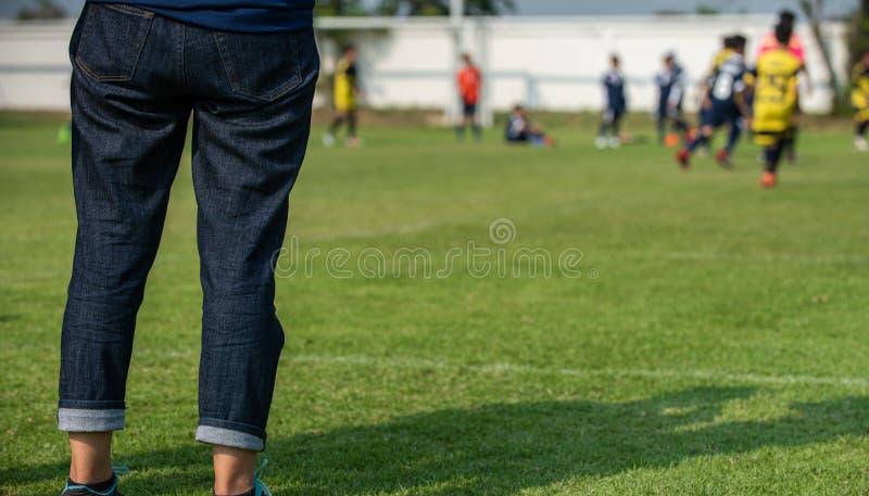 母亲身分和观看她的儿子踢在一次学校比赛的橄榄球在一清楚的天空和好日子 库存照片