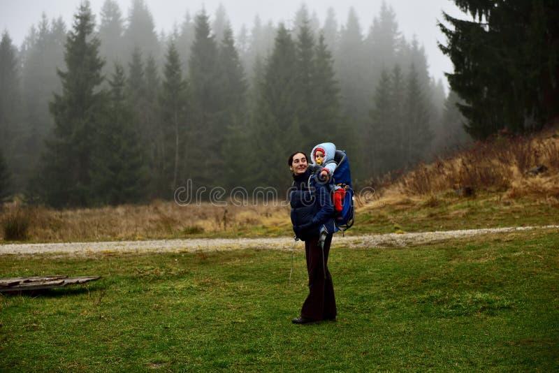 年轻母亲迁徙,运载她的婴孩背包的婴孩 免版税库存照片