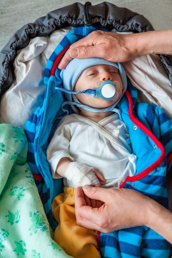 母亲递拿着一个病的婴儿男孩耐心对安慰者和绷带在他的手上 免版税库存照片