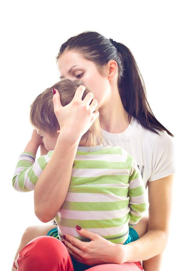 母亲镇定一个哭泣的孩子 免版税库存图片