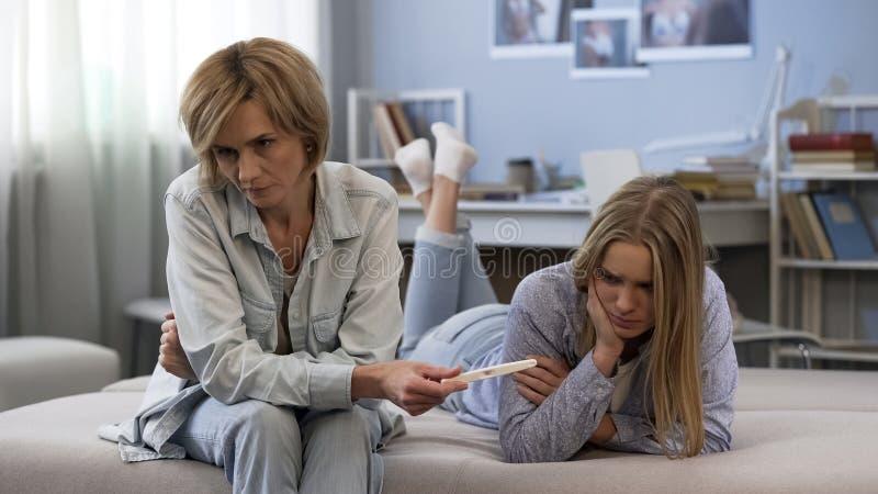 母亲陈列发现了两小条妊娠试验给羞愧的青少年的女儿,问题 免版税库存照片