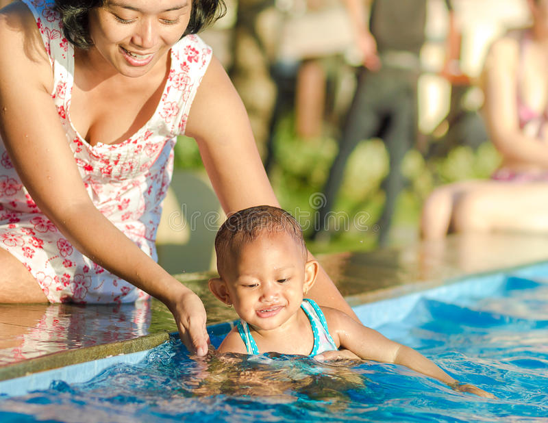 母亲鼓励小孩获得乐趣在游泳池 免版税库存图片