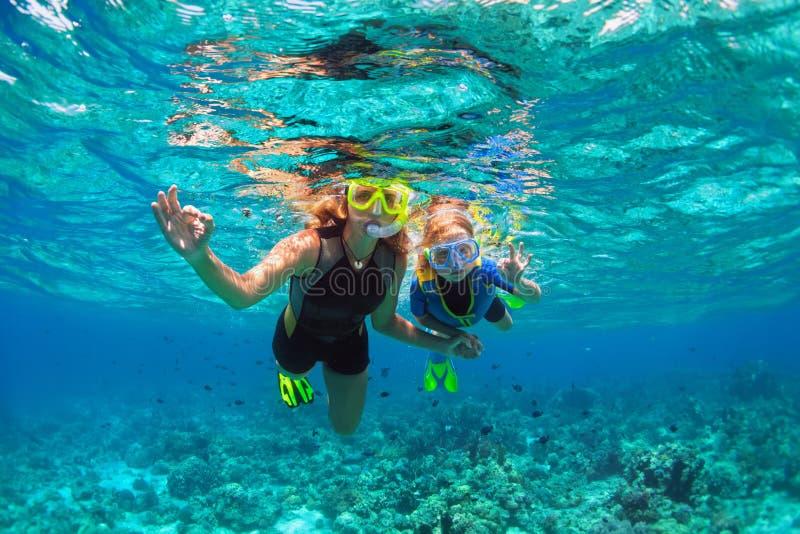 母亲,在潜航的面具下潜水中的孩子与热带鱼 免版税图库摄影