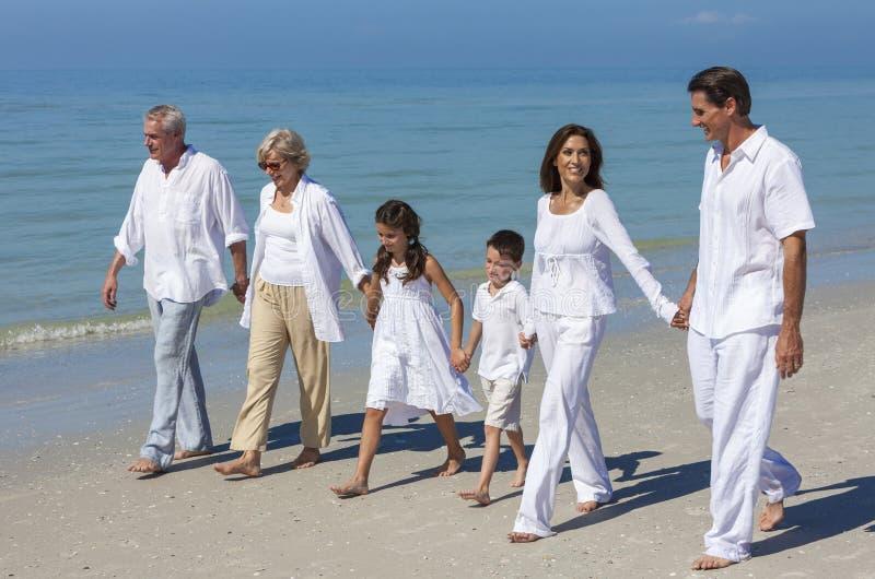 母亲,父亲Granparents,走在海滩的儿童家庭 库存图片