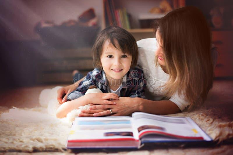 年轻母亲,读了一本书给她的孩子,男孩在客厅o 库存照片