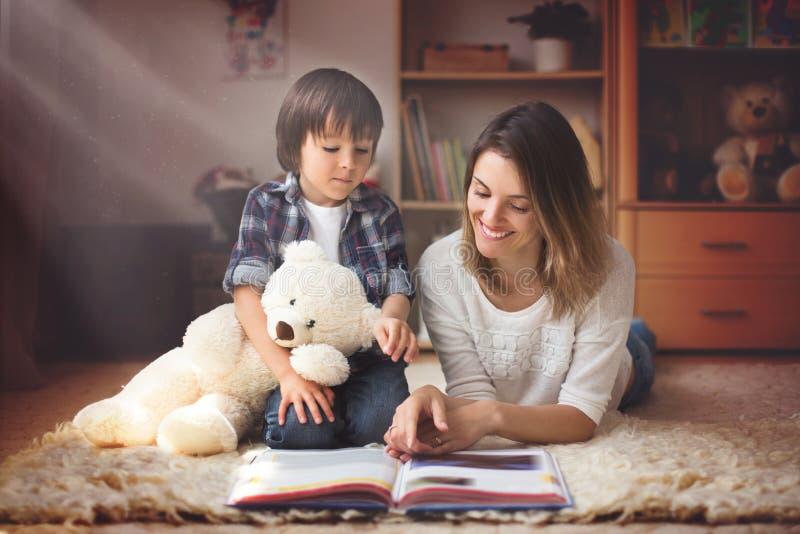 年轻母亲,读了一本书给她的孩子,男孩在客厅o 免版税库存图片