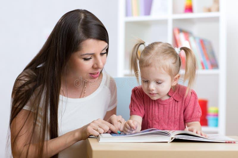 年轻母亲读一本书给她的儿童女儿 免版税库存图片