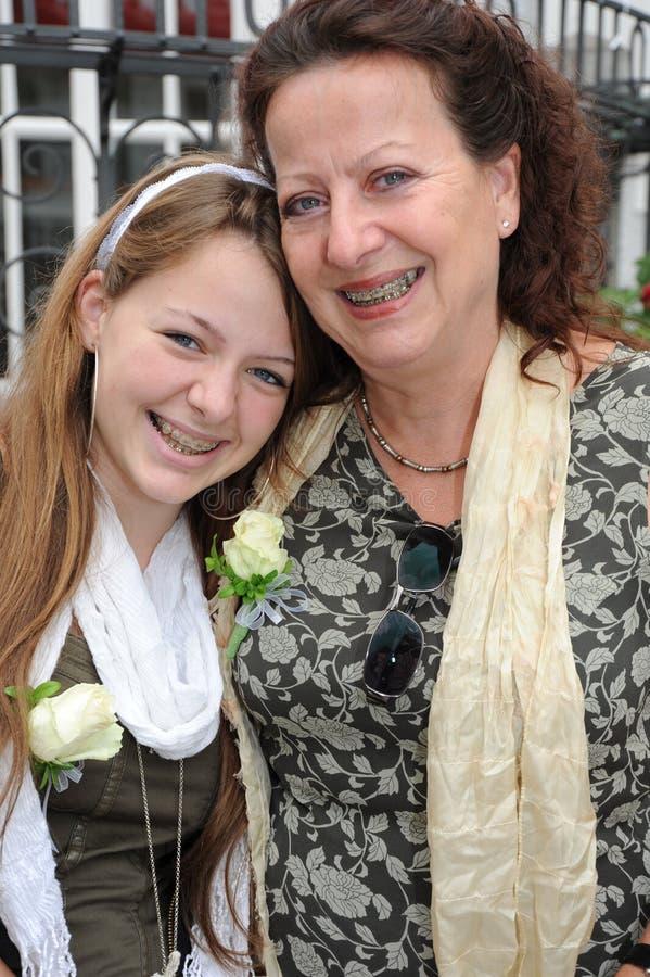 母亲-与大括号的女儿笑的纵向 图库摄影