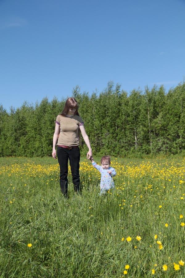 年轻母亲去与小儿子在绿色森林附近 库存图片