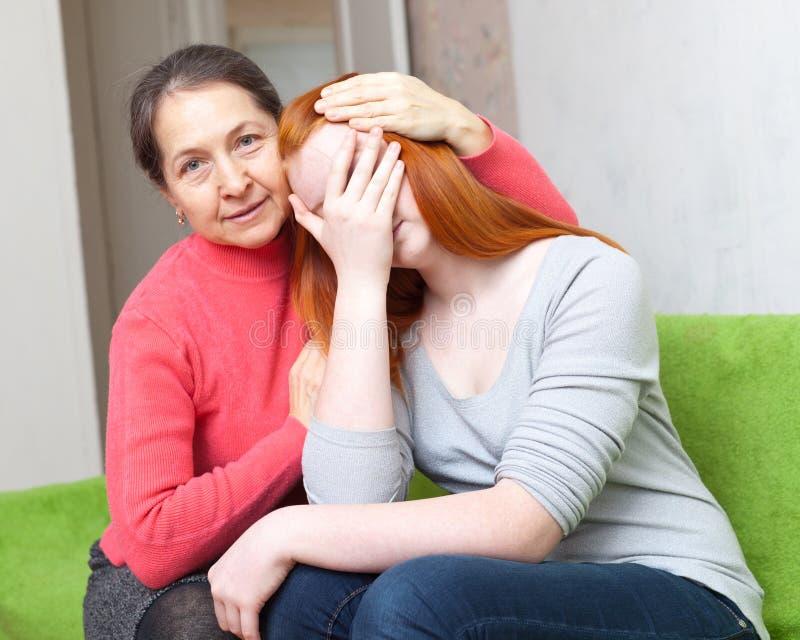母亲给安慰哭泣的女儿 免版税库存照片