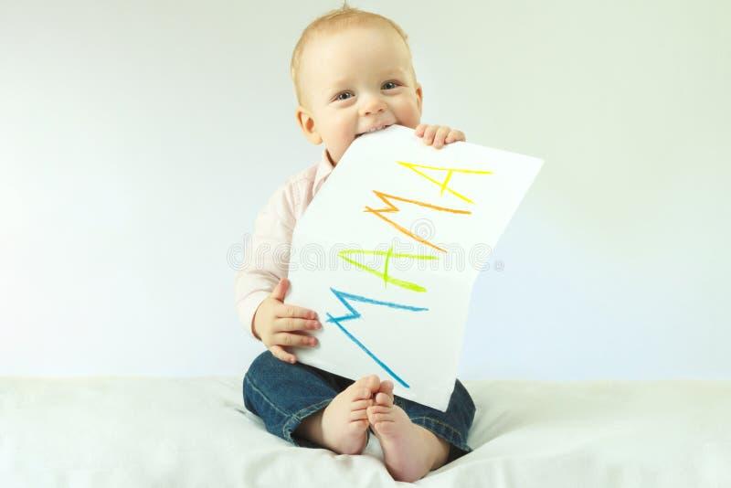 母亲-第一个词 拿着与标志妈妈的婴儿男孩大明信片 复制空间 日花产生母亲妈咪儿子 男孩微笑 免版税图库摄影