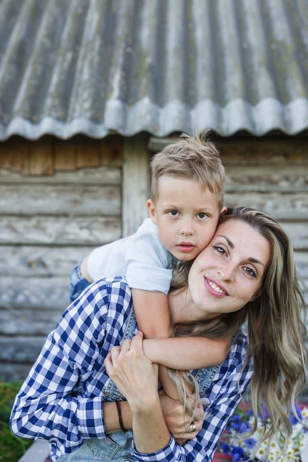 年轻母亲画象有一起站立在老减速火箭的木房子前面的儿子的 库存照片