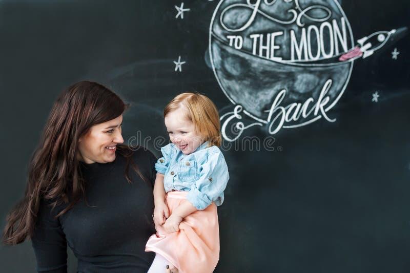年轻母亲画象有小女儿的以被装饰的墙壁为背景 免版税库存图片