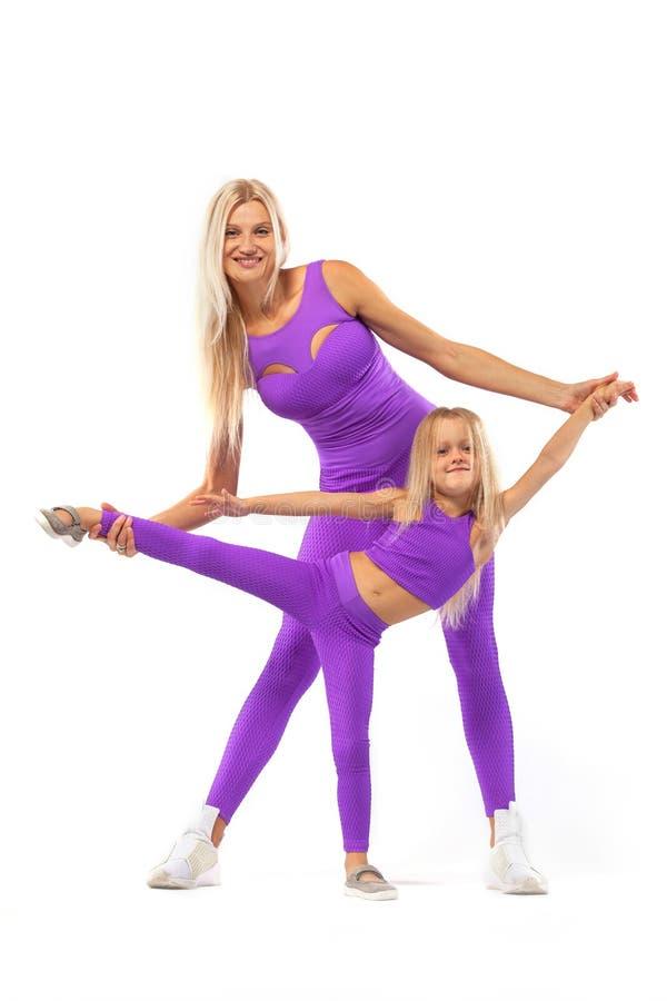 母亲` s日概念 户内一起年轻母亲和女儿锻炼健身 家庭神色 免版税库存图片