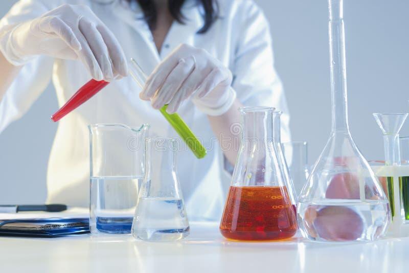 母实验室职员的手特写镜头与在烧瓶的液体标本一起使用在实验室 免版税库存图片