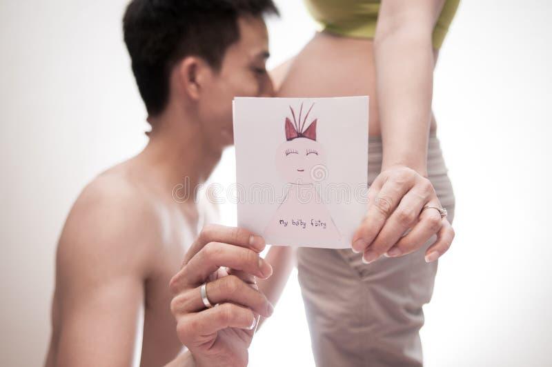 母性概念 夫妇爱可爱 他的妻子的人亲吻的腹部 等待新出生的婴孩的妈妈和爸爸 免版税图库摄影