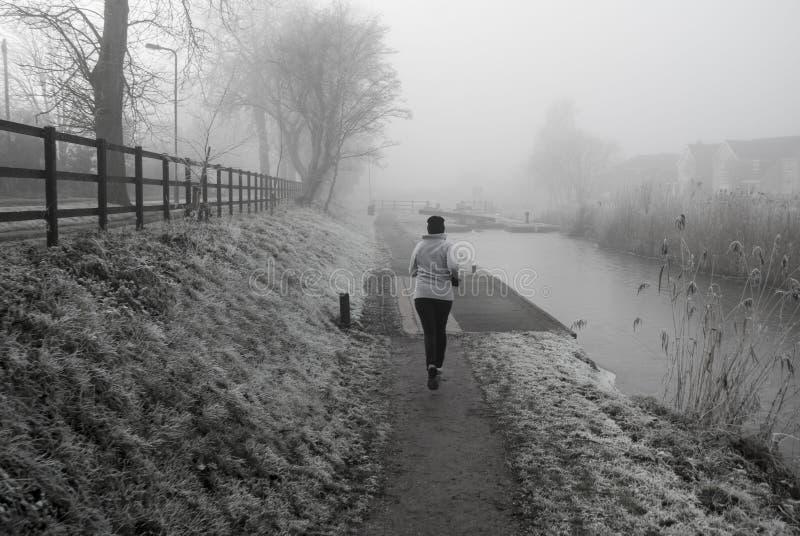 母慢跑者在冷的有薄雾的早晨 库存照片