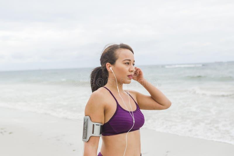 母赛跑者为在海滩安装耳机的室外锻炼做准备 免版税图库摄影