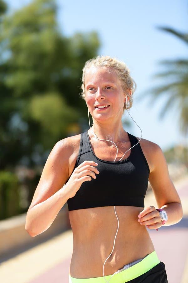 母赛跑者跑的听的智能手机音乐 库存照片