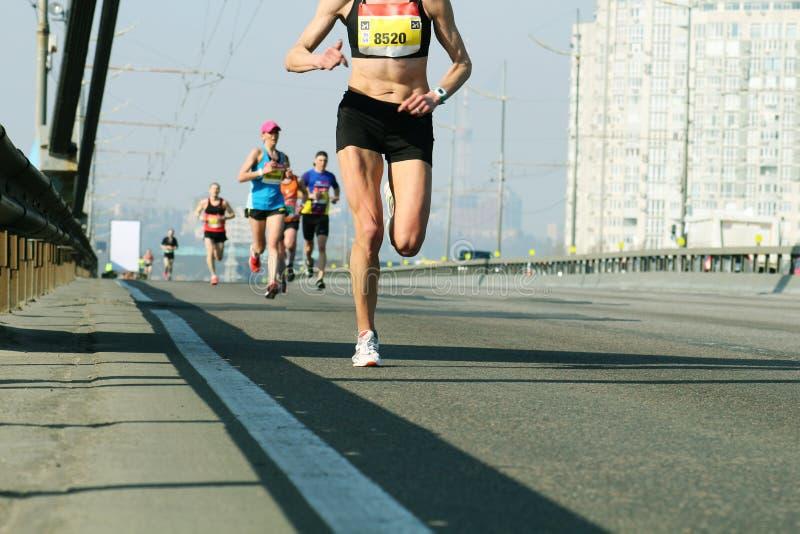 母领导运动员赛跑者连续城市马拉松 在城市桥梁路的年轻女人赛跑 马拉松赛跑早晨 免版税库存图片