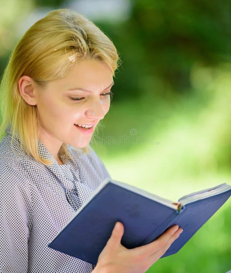 每个女孩应该读的书 女孩感兴趣坐公园读的书自然背景 读富启示性的书 女性 免版税库存图片