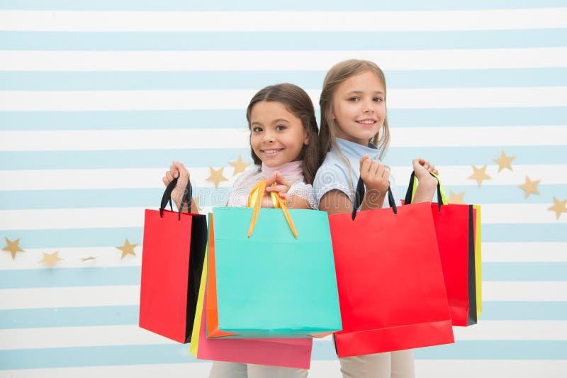 每女孩购物梦想与最好的朋友一起的 女孩儿童最好的朋友拿着束购物袋 库存照片