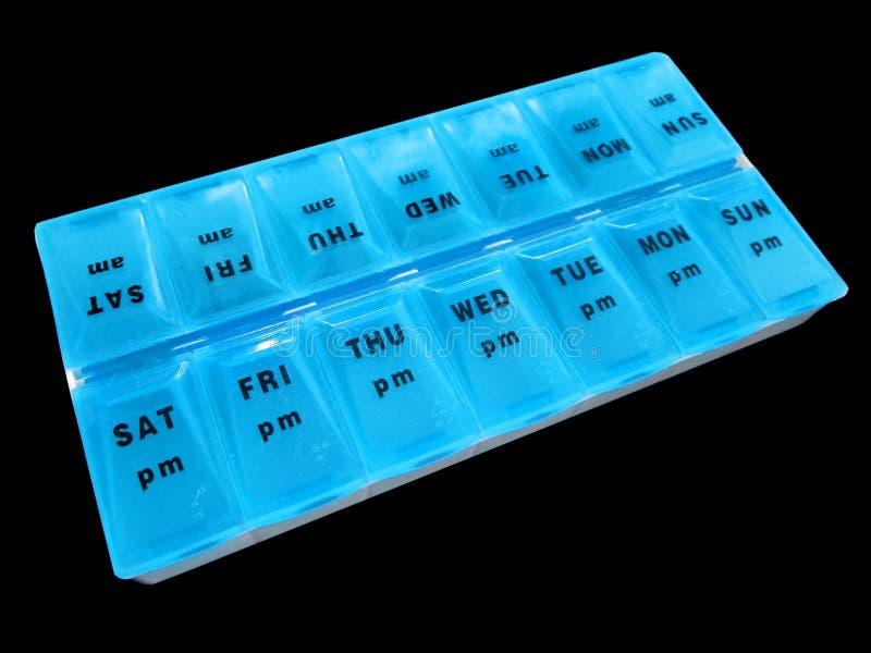 每日在黑背景天隔绝的疗程药物分配器药片维生素蓝色药片箱子星期 免版税库存照片