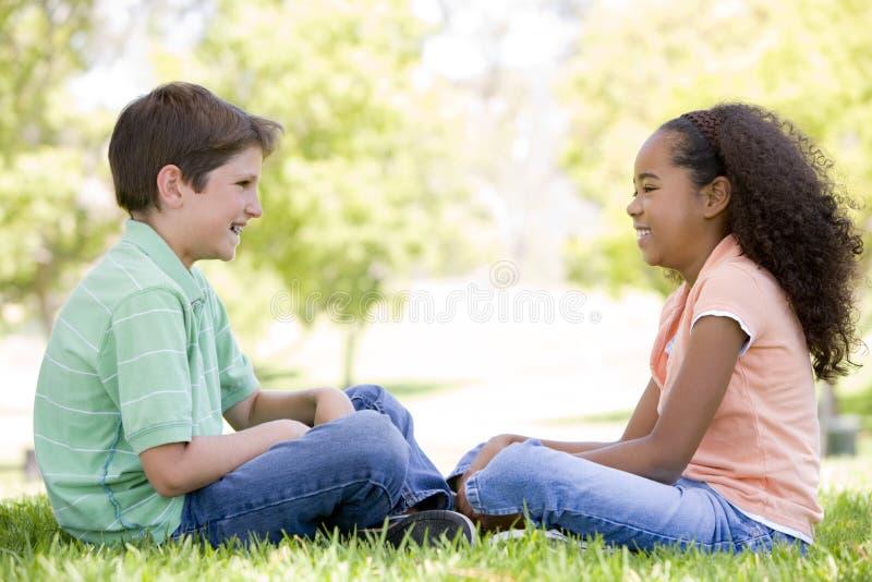 每查找户外坐的拖曳年轻人的朋友 免版税图库摄影