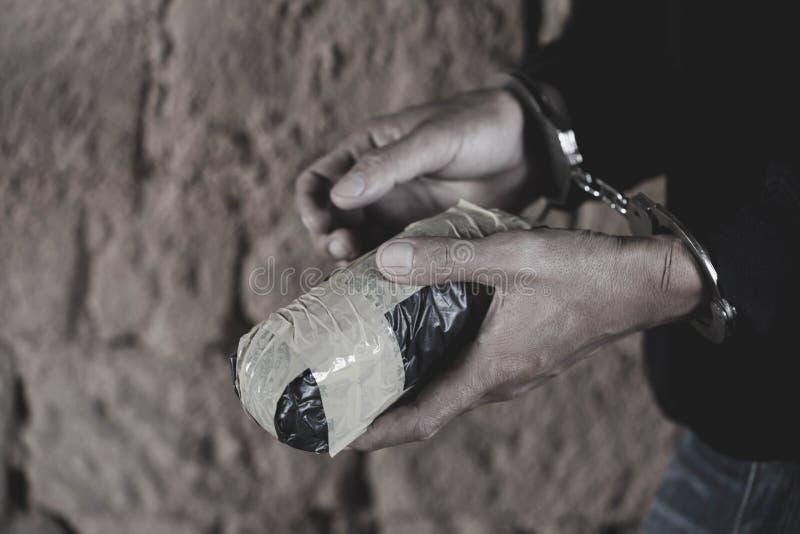 毒贩被拘捕限制与手铐与海洛因,法律和警察概念一起 世界反对服用麻醉品的天 库存照片