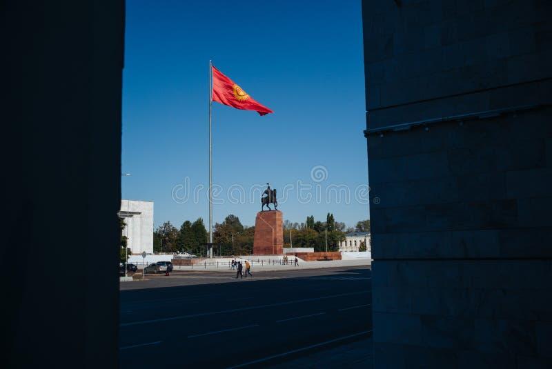 比什凯克,吉尔吉斯斯坦:挥动在旗杆的太丙氨酸正方形吉尔吉斯旗子有英雄玛纳斯雕象和状态历史博物馆观点的 免版税库存照片