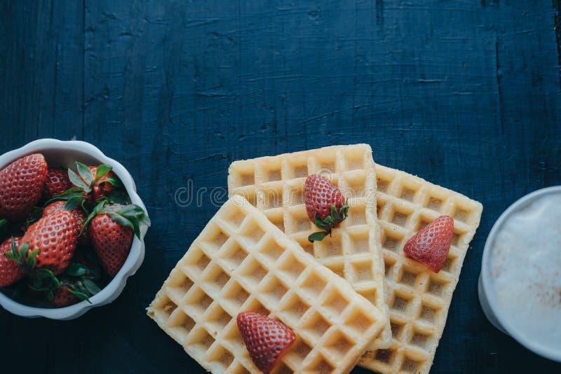 比利时华夫饼干、草莓和咖啡在白色杯子 空间为 免版税库存照片