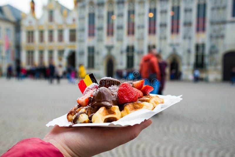 比利时奶蛋烘饼用巧克力汁和草莓,布鲁日市背景 免版税库存照片