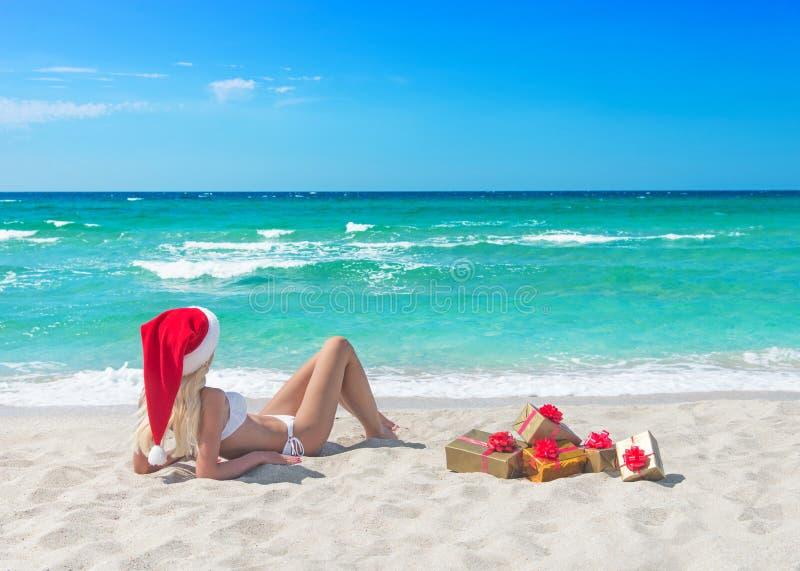 比基尼泳装、红色圣诞节帽子和礼物盒的美丽的白肤金发的妇女 免版税库存照片