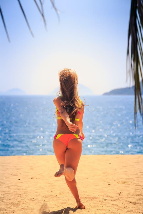 比基尼泳装后侧方的白肤金发的女孩跑到海手后边  库存照片