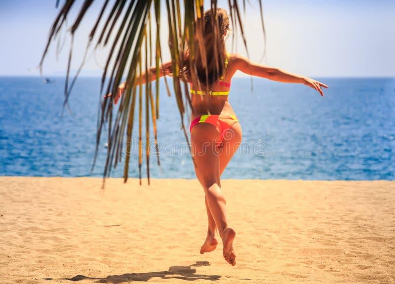 比基尼泳装后侧方视图的白肤金发的亭亭玉立的体操运动员跳过沙子 库存图片