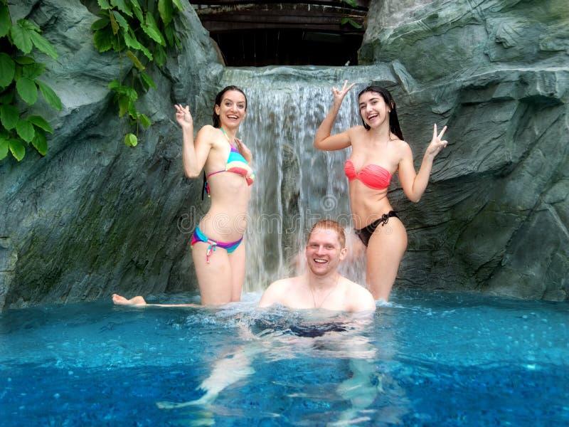 比基尼泳装和享用瀑布的落的水的在水池的一个人的两名年轻性感的妇女 免版税库存照片