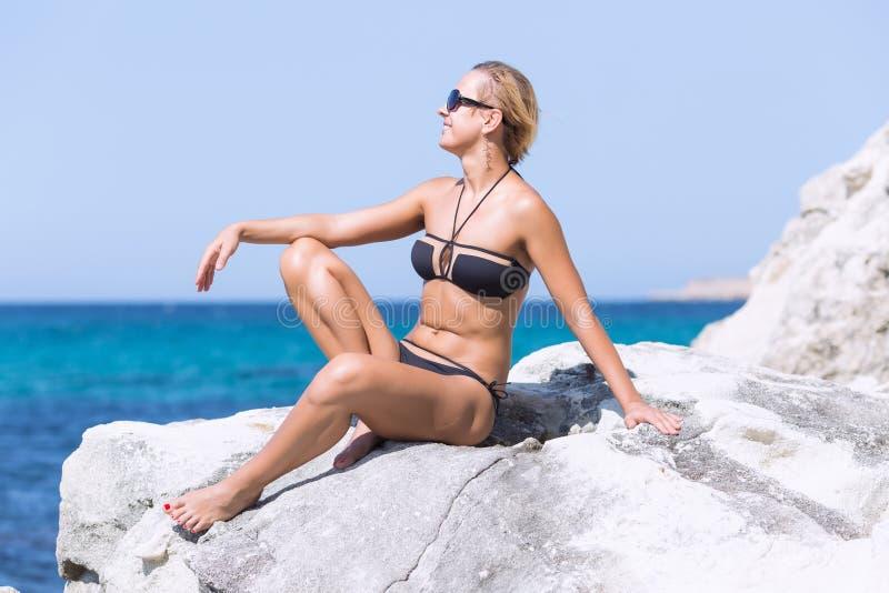 比基尼泳装和太阳镜的被晒黑的白肤金发的妇女在海 免版税库存照片
