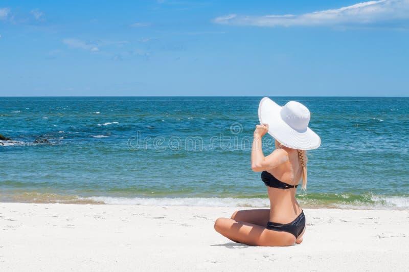 比基尼泳装和帽子的美丽的妇女坐海滩享受暑假的 免版税库存图片