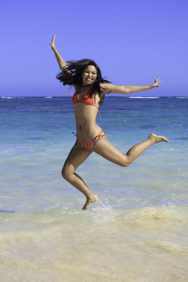 比基尼泳装女孩跳的红色 免版税图库摄影