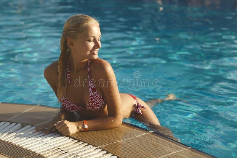 比基尼泳装姿势的美丽的时兴和性感的白肤金发的女孩在游泳池 免版税库存照片