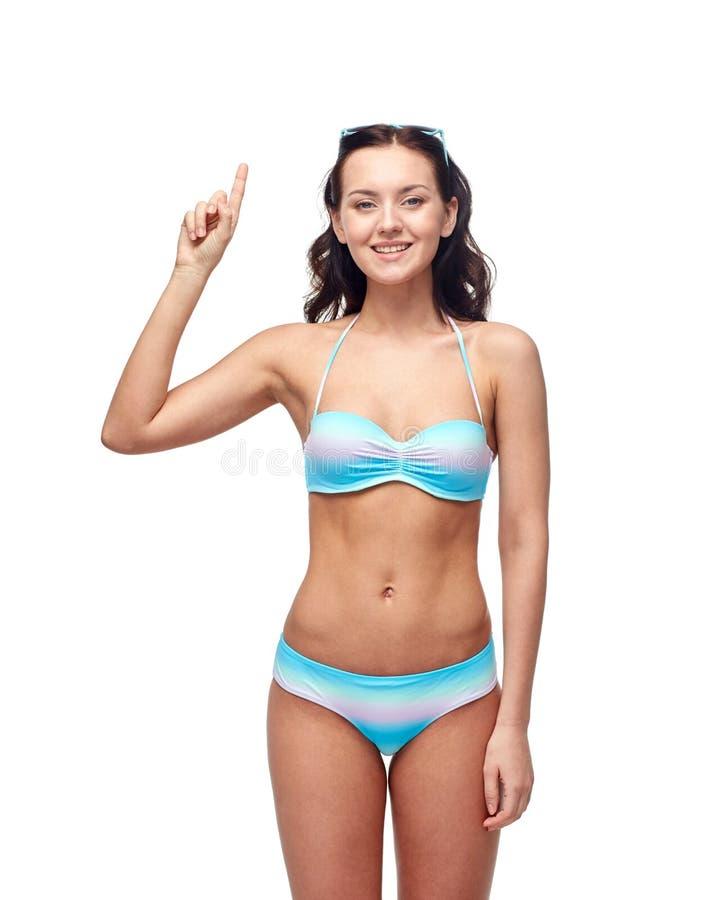 比基尼泳装泳装的愉快的妇女指向手指的  库存图片
